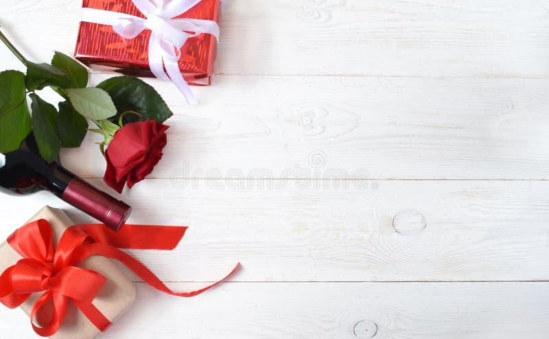 红色玫瑰、一个瓶酒和礼物 免版税图库摄影