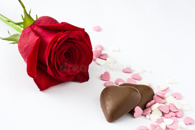 红色玫瑰、巧克力糖果与心脏形状和糖果 免版税库存图片