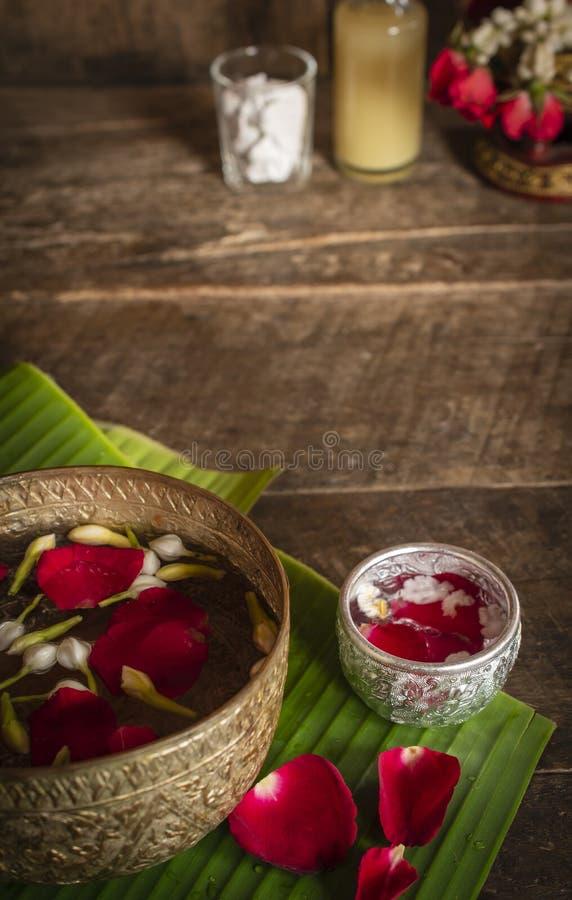 红色玫瑰、茉莉花和流行的米在木桌安置的镇静水表面上准备好为倾倒水在手尊敬之上 库存照片