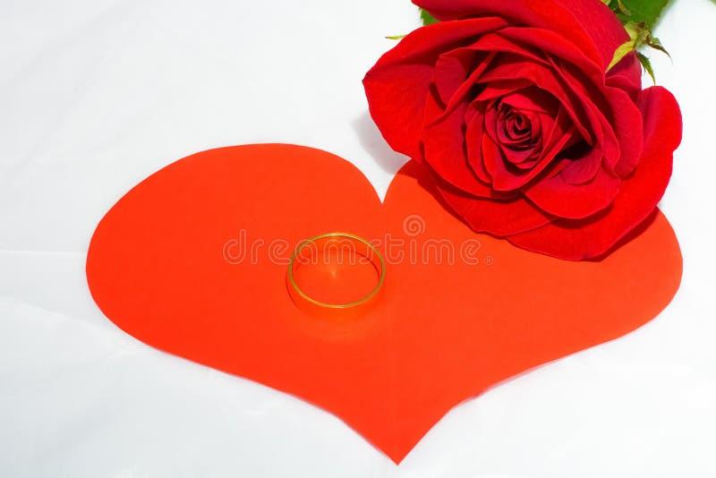 红色玫瑰和纸心脏,金子圆环  库存照片
