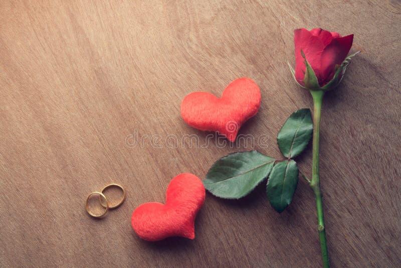 红色玫瑰和金子与心脏的定婚戒指在木塑造 免版税图库摄影