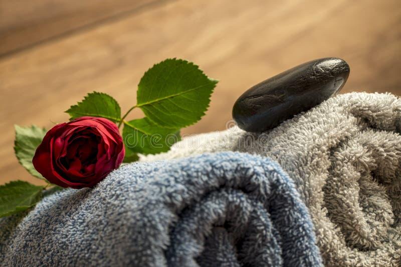 红色玫瑰和黑禅宗按摩在蓝色和白色的石头滚动 免版税库存照片