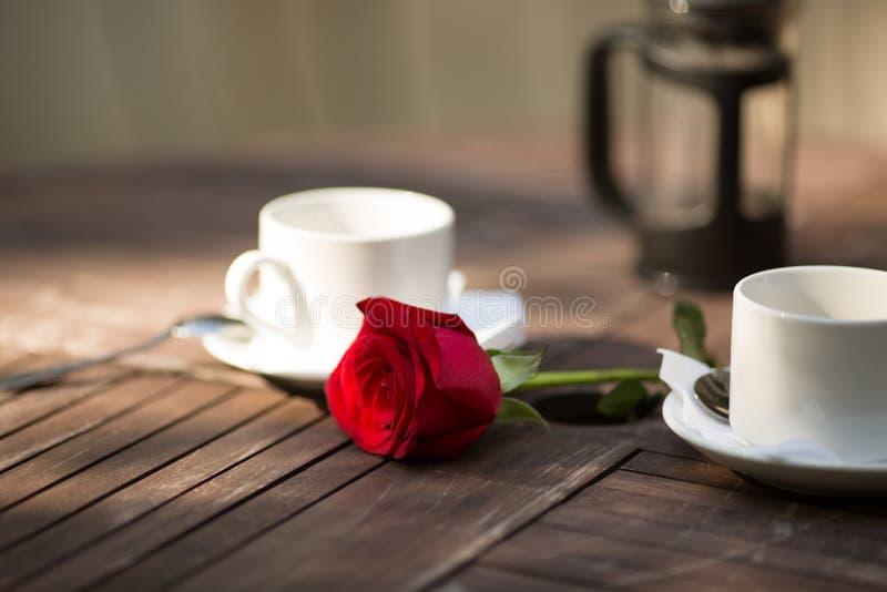 红色玫瑰在桌上的两个杯子 库存照片