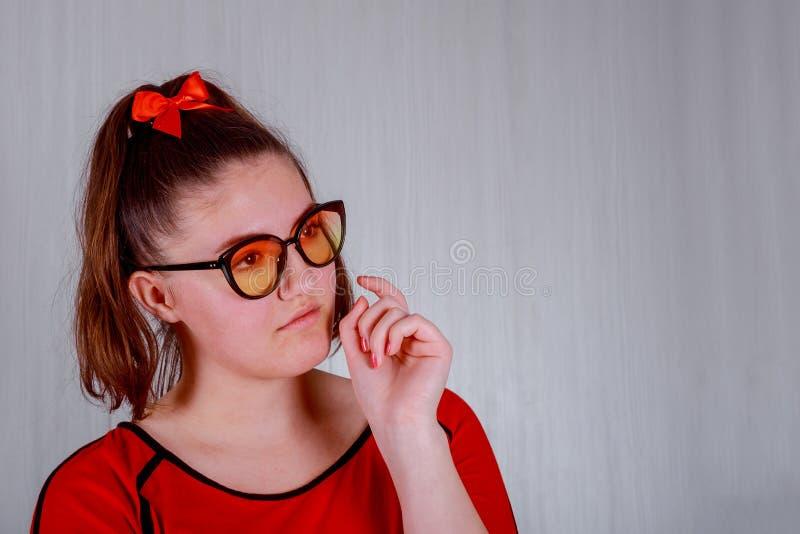 红色玻璃的一个俏丽的在灰色背景位的女孩和a她的嘴唇 免版税库存照片