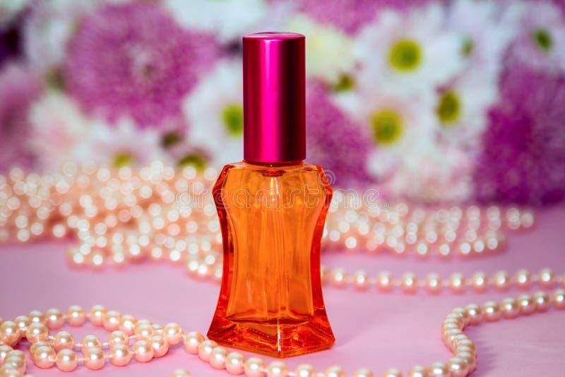 红色玻璃香水瓶和珍珠小珠 免版税库存图片