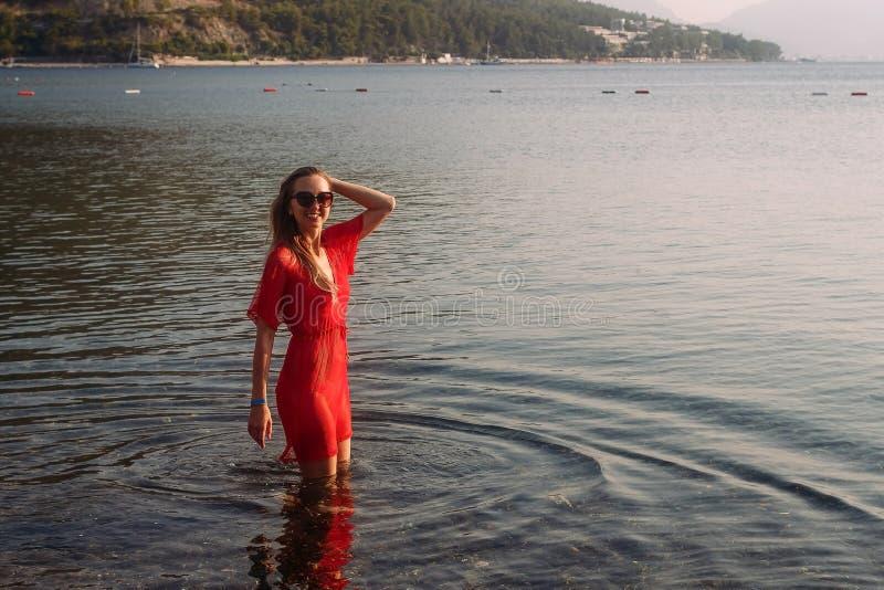 红色班丹纳花绸和长袍立场的微笑的年轻白种人妇女在海 库存图片