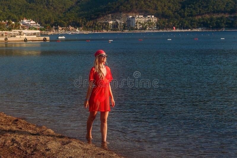 红色班丹纳花绸的走由海的微笑的年轻白种人妇女和长袍 免版税库存照片