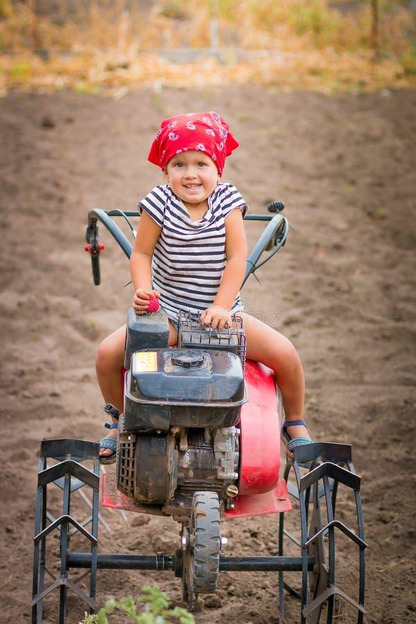 红色班丹纳花绸和条纹发球区域的愉快的孩子坐在领域的翻土机 女婴司机耕地机 库存照片