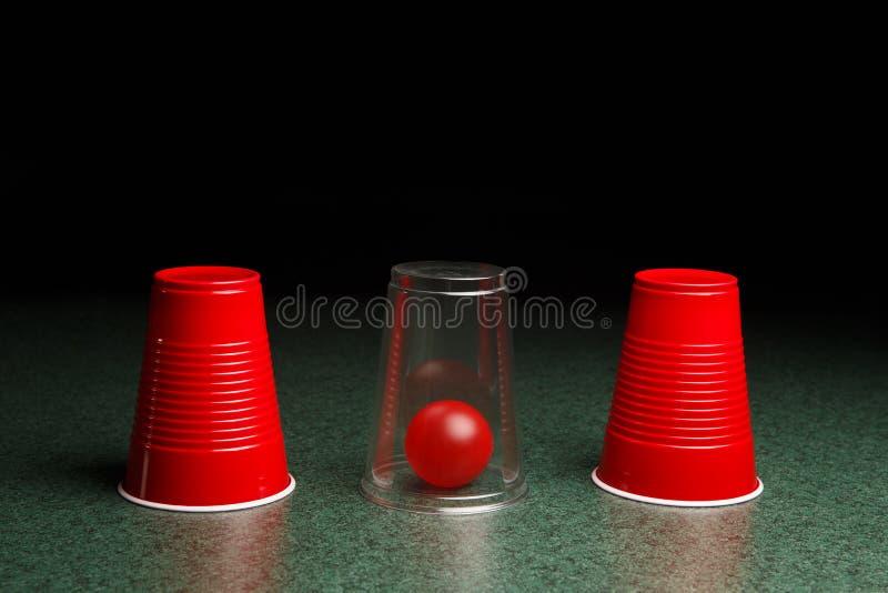 红色球掩藏在清楚的杯下 免版税图库摄影
