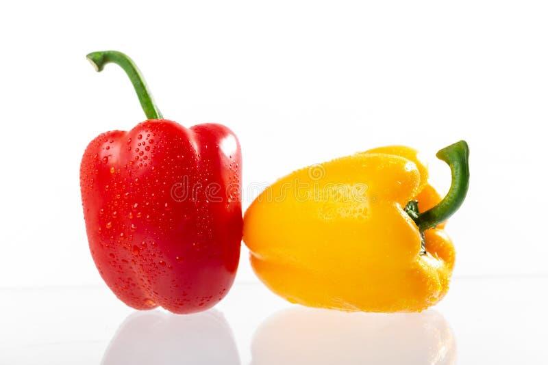 红色甜椒和黄色喇叭花胡椒与水下落在白色背景 免版税库存照片