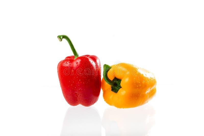 红色甜椒和黄色喇叭花胡椒与水下落在白色背景 库存照片