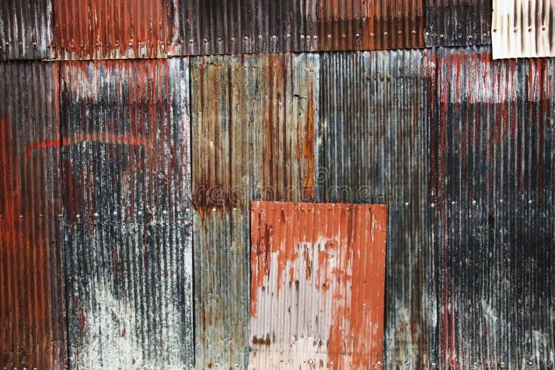 红色生锈的波纹状的金属铁的板料和蓝色背景影像  图库摄影