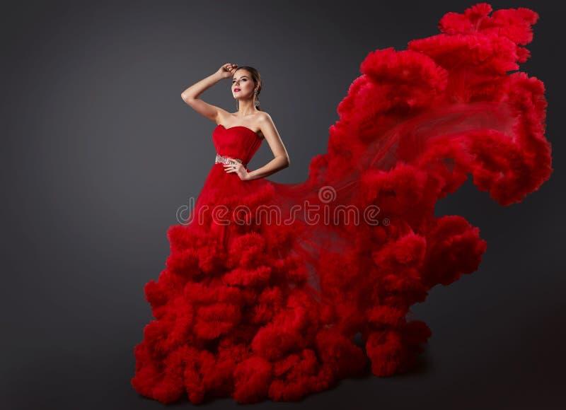 红色用褶裙饰边的礼服的,在云彩褂子的时装模特儿妇女有长的挥动的飞行稳定尾翼的 免版税库存图片