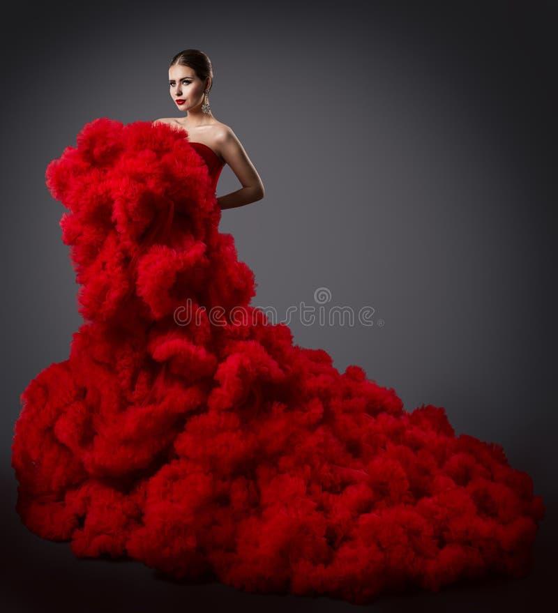 红色用褶裙饰边的礼服的,在长的蓬松挥动的褂子的时装模特儿妇女 免版税图库摄影