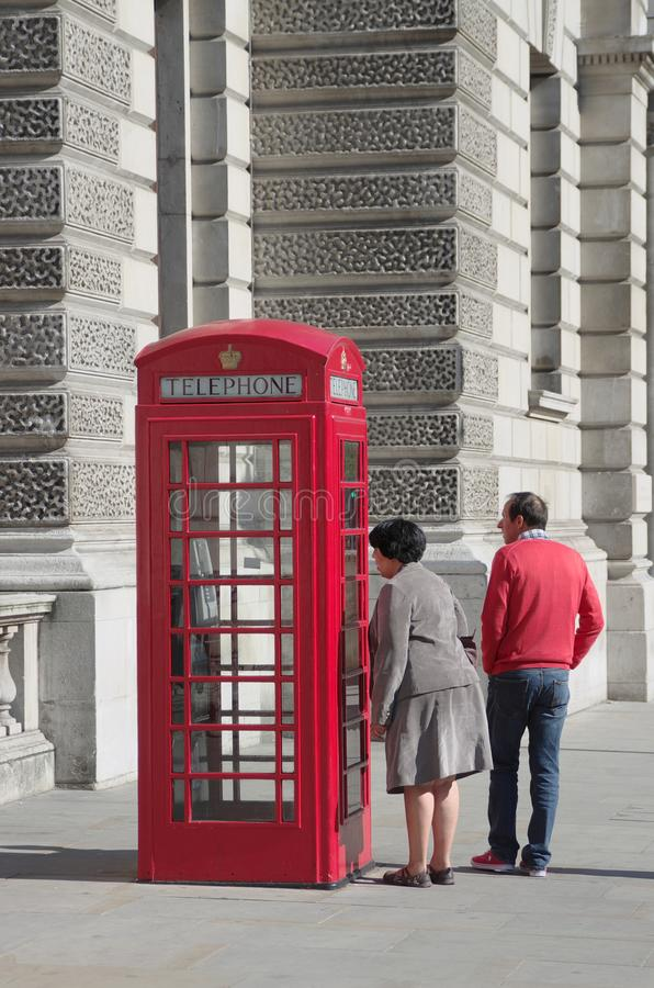 红色电话亭和一个好奇游人 免版税库存图片