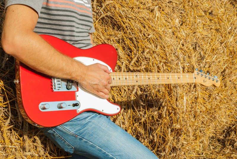 红色的吉他电视广播员与一张木邮票在秸杆音乐家背景的手上在一个晴朗的夏日 免版税库存照片