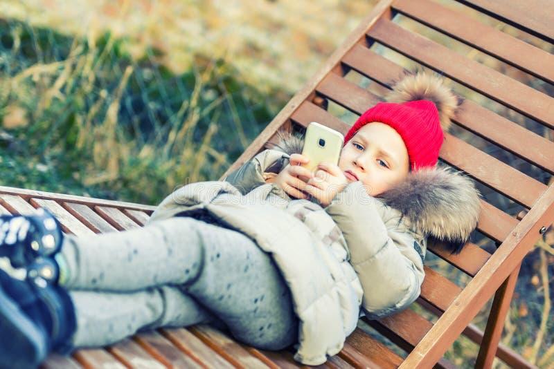 红色的小逗人喜爱的白种人白肤金发的小孩女孩编织了说谎在休息室和拿着smartphon的帽子和温暖的夹克手中 Ou 免版税库存照片