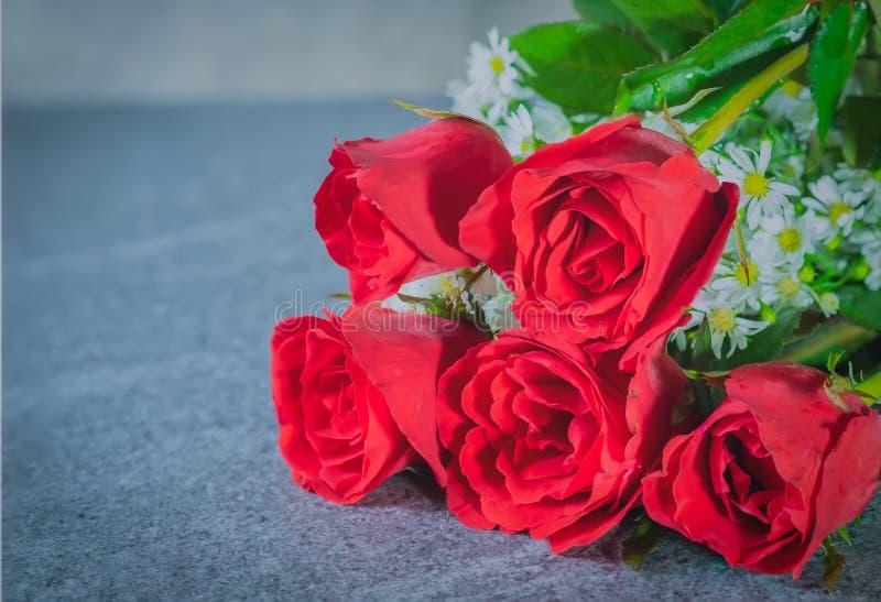 红色的玫瑰和在石桌安置的白花 免版税库存照片