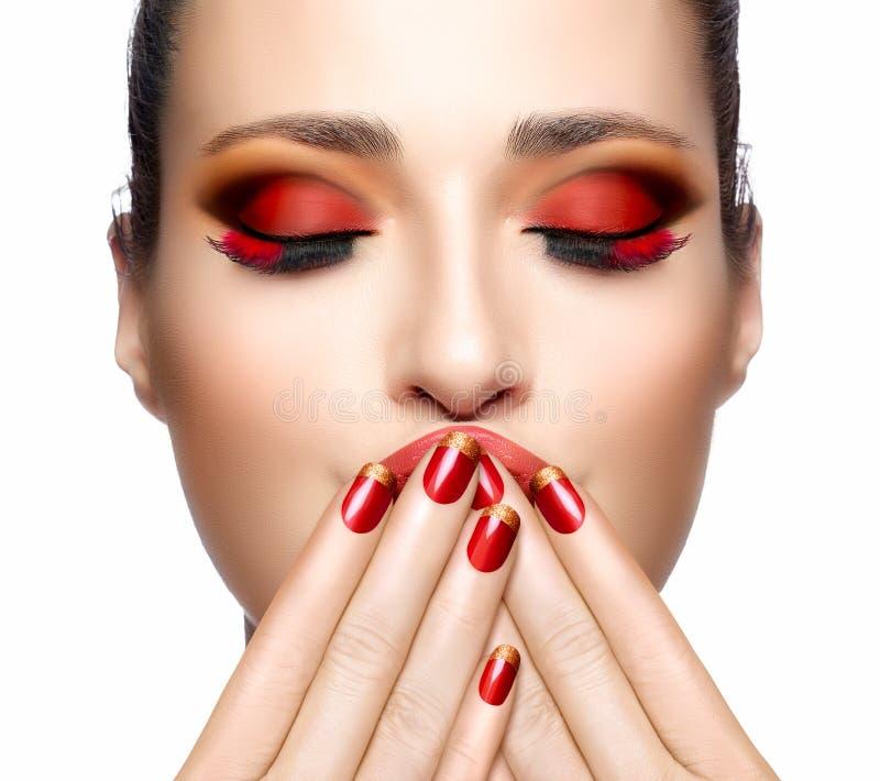 红色的美丽的女孩用在她的面孔的手 钉子艺术和Makeu 免版税库存照片