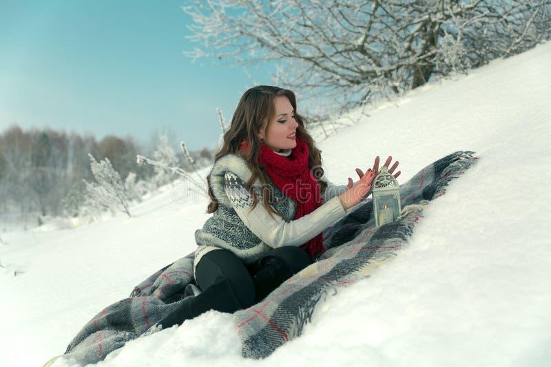 红色的美丽的愉快的深色的女孩在树背景的冬天编织了围巾坐在雪的一条毯子  免版税库存照片