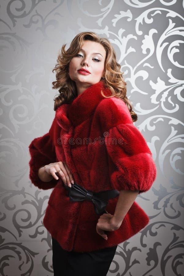 红色皮大衣的美丽的女孩 免版税库存照片