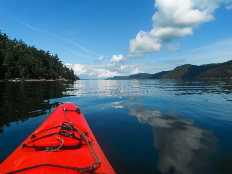 红色皮船和蓝天在水中 库存图片