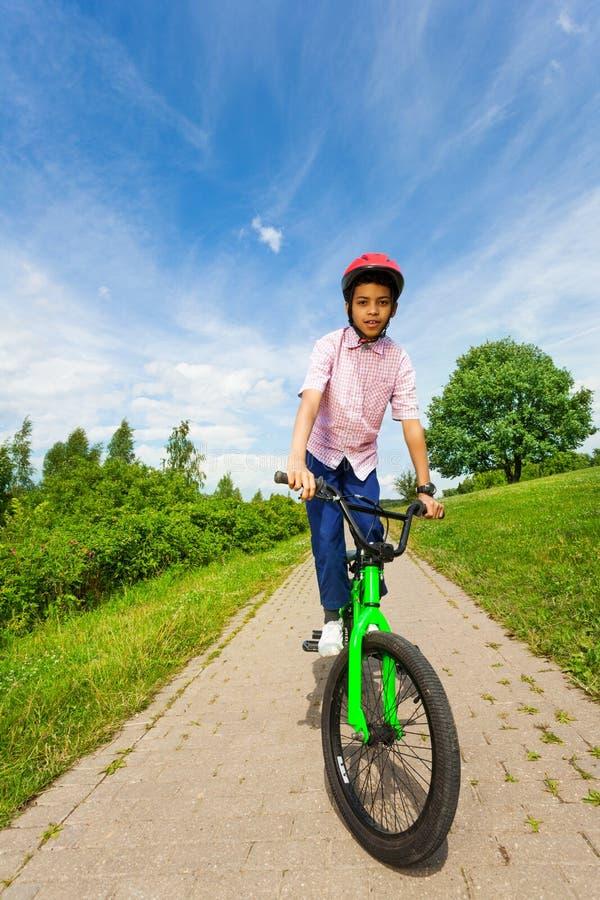 红色盔甲的非洲男孩骑鲜绿色的自行车 免版税库存照片