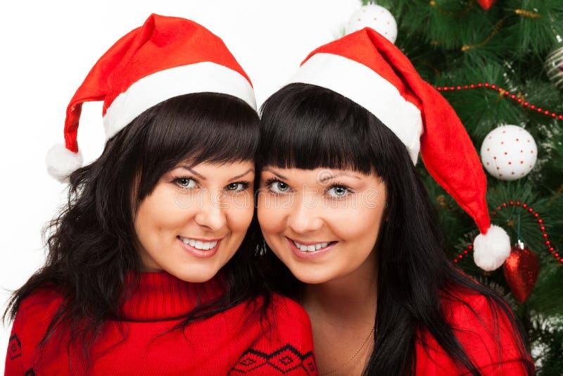 红色盖帽微笑的二个女孩在圣诞树附近 免版税库存照片