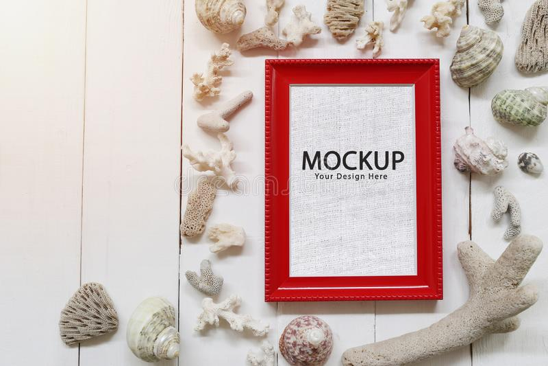红色相框安置在一个白色木地板和与壳和白海珊瑚 库存图片