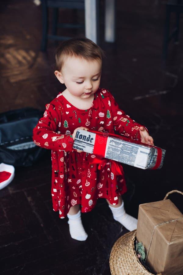 红色睡衣礼服开头圣诞节礼物的愉快的相当小女孩 免版税图库摄影