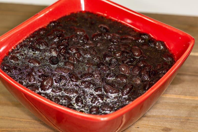 红色碗用黑豆汤填装了立即可食在厨房用桌上 库存照片