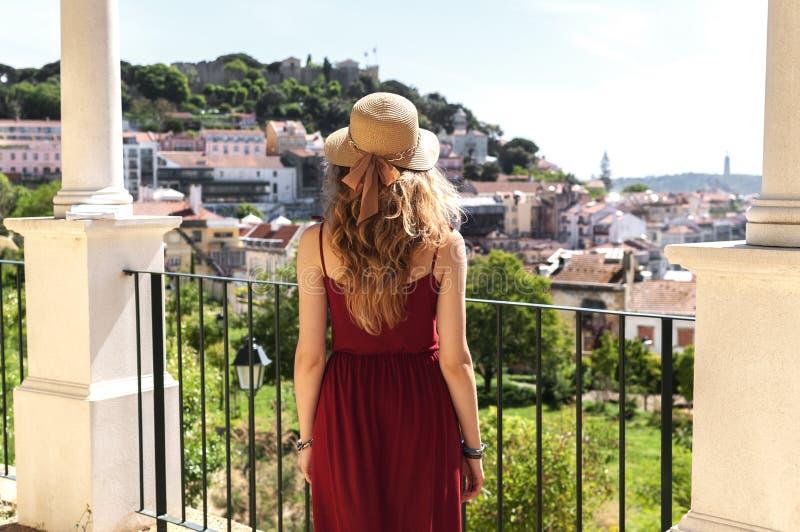 红色礼服、太阳帽子和蓝色袋子lookimg的妇女在全景图im里斯本Alfama,葡萄牙 库存照片