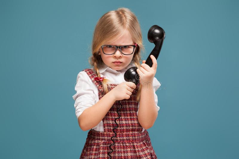 红色礼服、白色衬衣和玻璃的可爱的小女孩拿着电话手机 库存照片