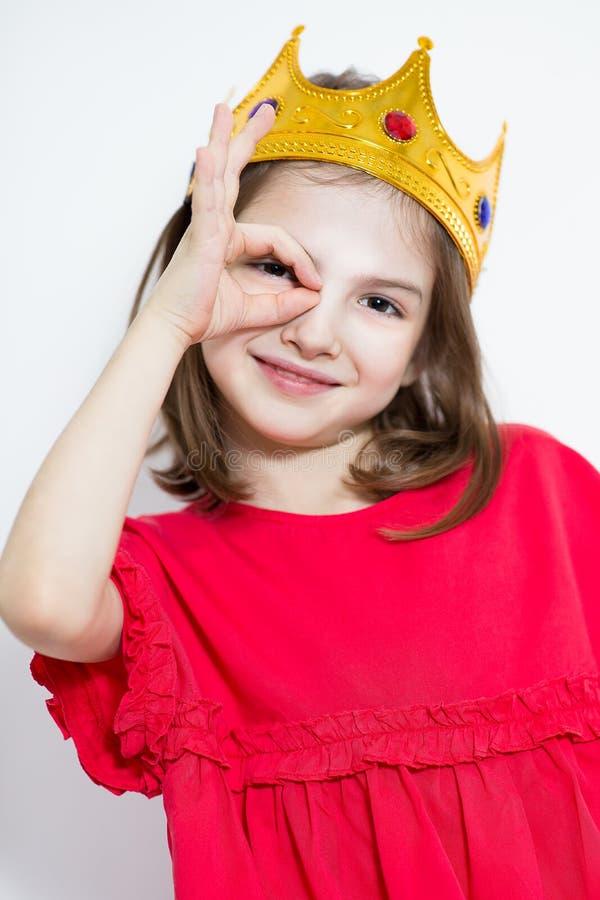 红色礼服和冠的迷人的小公主 库存图片