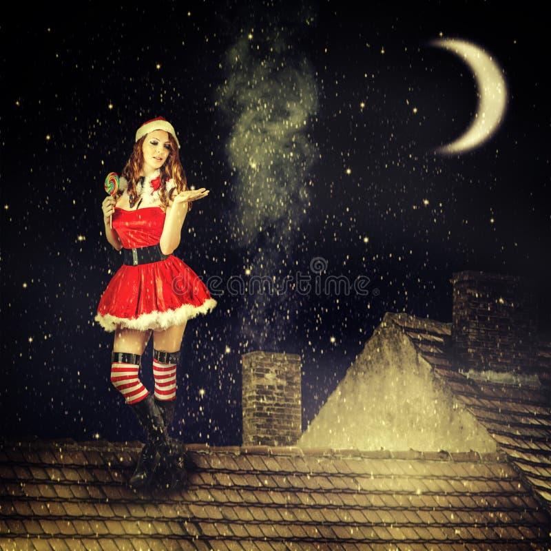 红色礼服和圣诞老人帽子的圣诞节神仙的妇女 库存照片