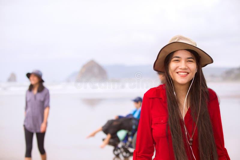红色礼服和帽子的两种人种的青少年的女孩在海滩 免版税库存照片