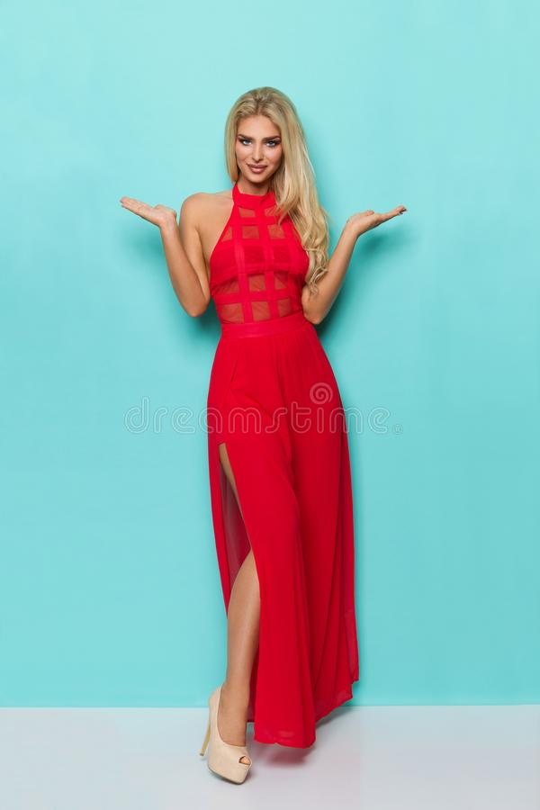 红色礼服和高跟鞋的美丽的白肤金发的妇女站立用被举的手 免版税库存图片