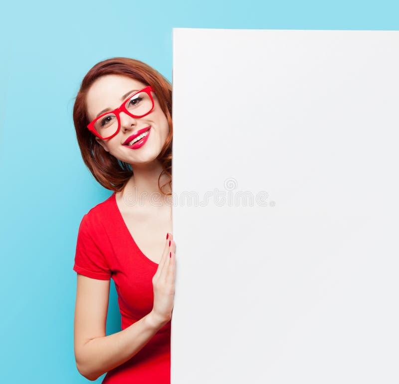 红色礼服和玻璃的女孩与白板 免版税库存图片