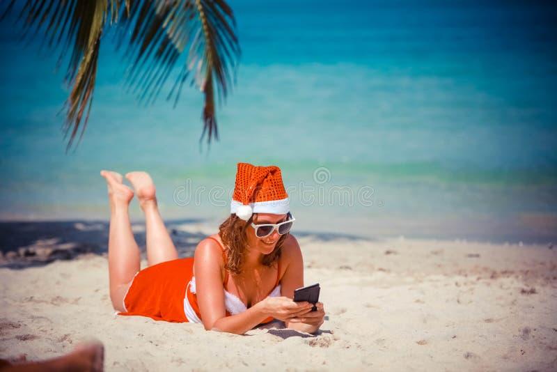 红色礼服和说谎在异乎寻常的热带海滩的圣诞老人帽子的逗人喜爱的白肤金发的妇女在棕榈树使用手机 节假日 库存照片