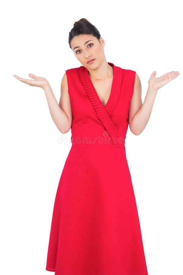 红色礼服摆在的犹豫的典雅的浅黑肤色的男人 免版税库存图片