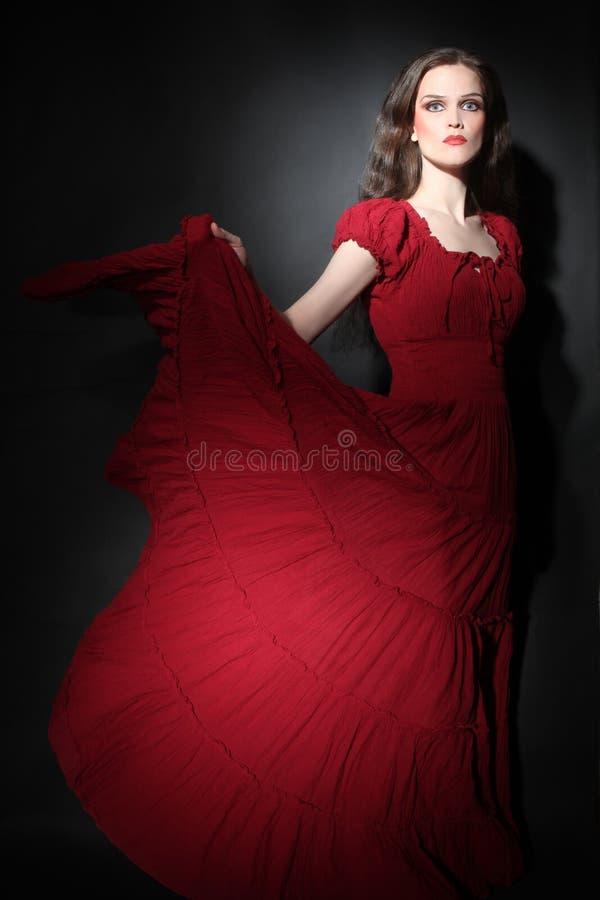 红色礼服时装模特儿的端庄的妇女 库存图片