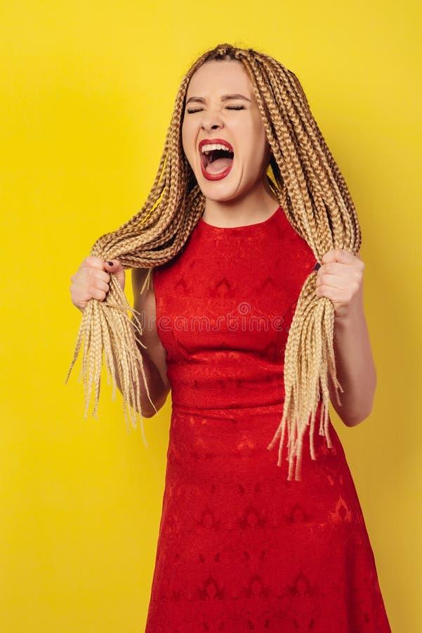 红色礼服的不满意的女孩呼喊保持她的非洲猪尾 库存照片