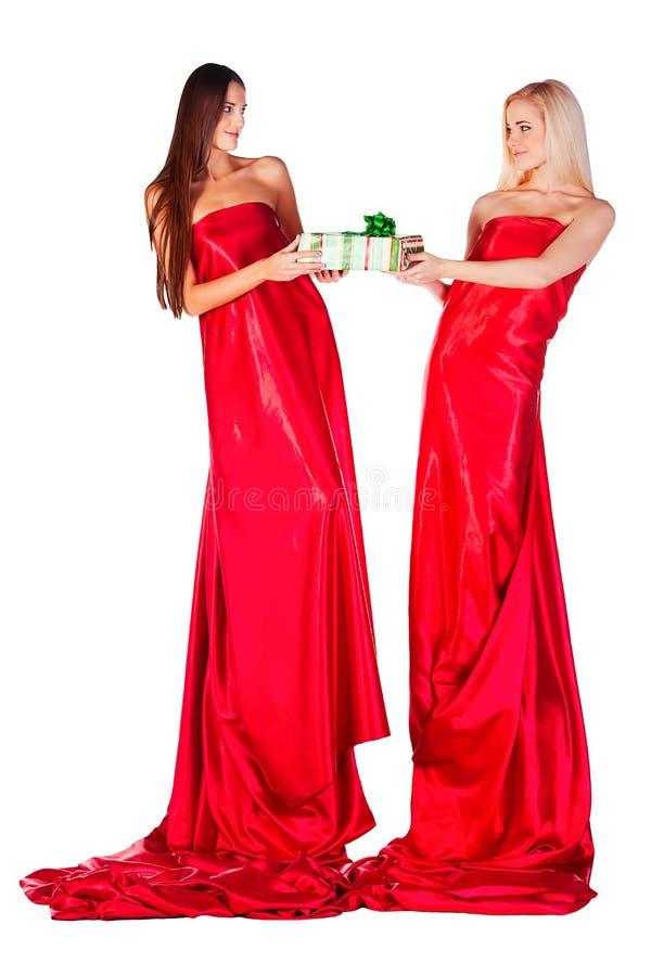 红色礼服的两名妇女有礼物的在看对中的每一的手上在地平线上方 库存图片