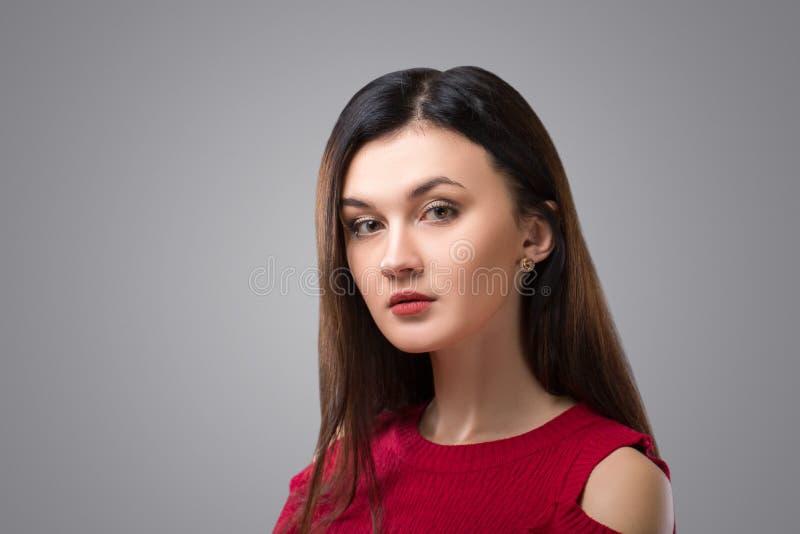 红色礼服的俏丽的深色的妇女在灰色背景 免版税库存图片