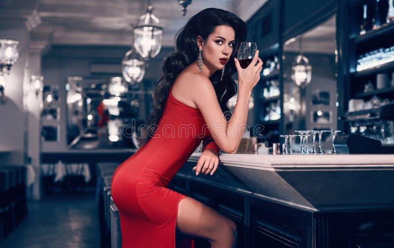 红色礼服的华美的年轻深色的妇女用酒 免版税库存图片