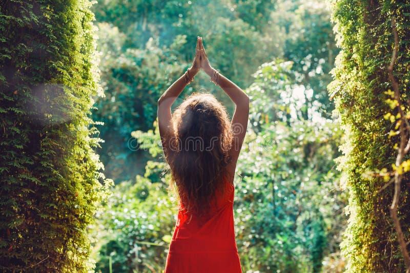 红色礼服的可爱的少妇在森林里 免版税库存图片