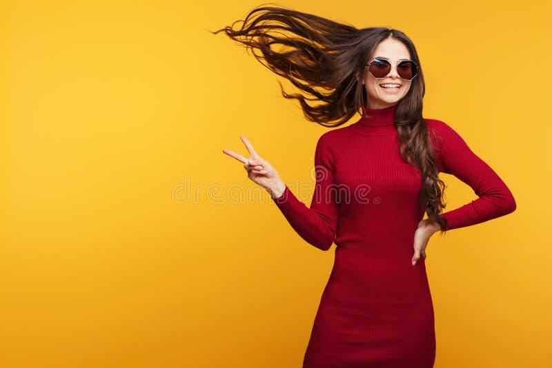 红色礼服的可爱的少妇摆在用在臀部的手并且显示和平手标志 免版税库存照片