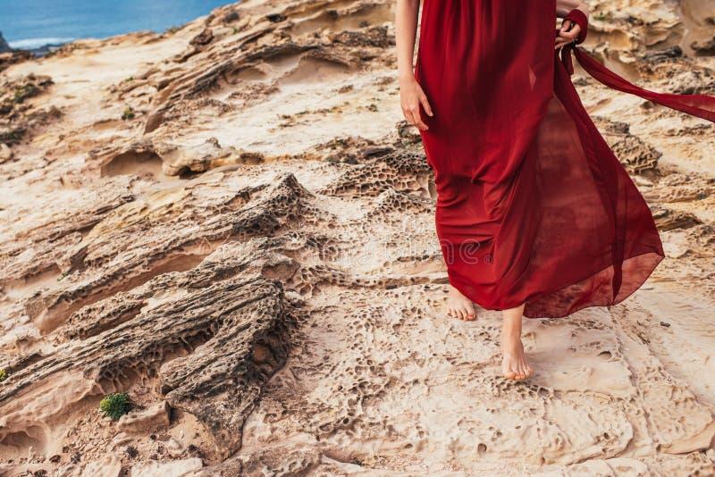 红色礼服的女孩在岩石和峭壁中沿海阿尔加威 免版税库存照片