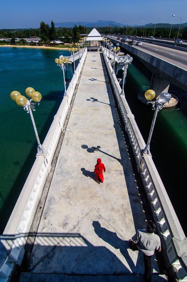 红色礼服的女孩在桥梁 免版税图库摄影