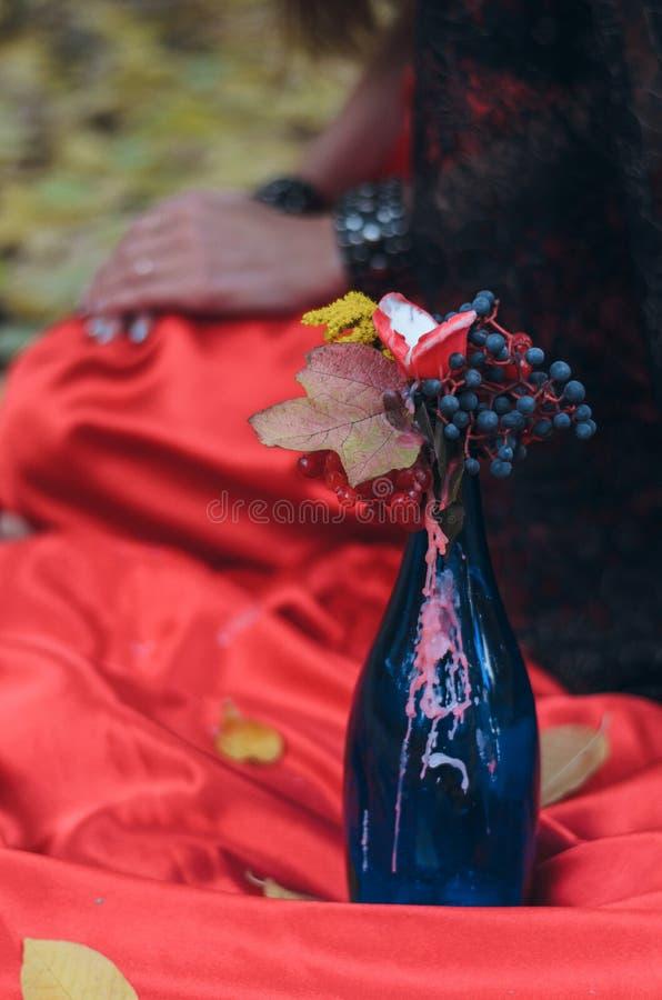 红色礼服的女孩在花束的森林蜡烛退色 免版税库存图片
